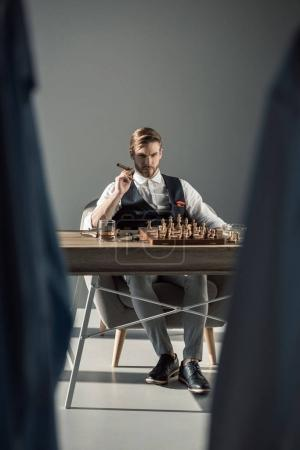 selective focus of young businessman with cigar looking at camera while playing chess