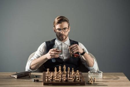 Photo for Young businessman with glass of whisky and cigar looking at camera while playing chess - Royalty Free Image