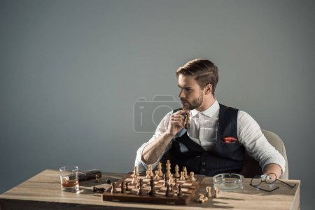 young man smoking cigar and looking away while playing chess