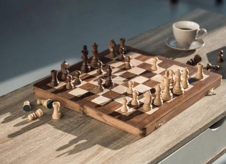 close-up view of chess board with pieces and cup of coffee on wooden table