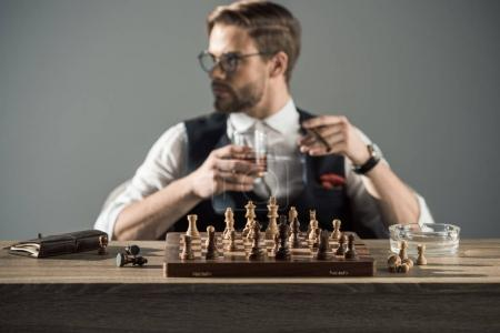 close-up view of chess board with figures and man drinking whisky and smoking cigar behind