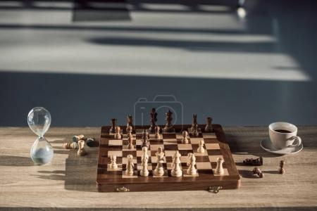 close-up view of chess board with pieces, cup of coffee and sand clock on table