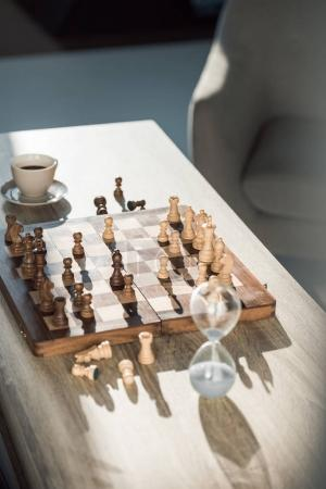 selective focus of chess board with pieces, cup of coffee and sand clock on table