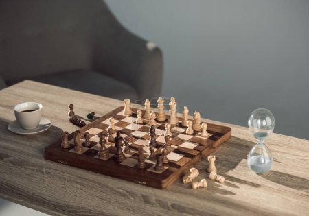 Photo for Close-up view of chess board with pieces, cup of coffee and sand clock on table - Royalty Free Image