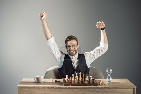 triumphing young busnessman in eyeglasses smiling at camera while playing chess