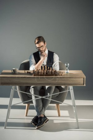 Photo for Thoughtful young businessman in eyeglasses playing chess - Royalty Free Image
