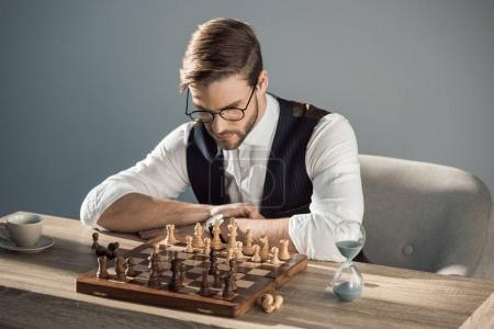 concentrated young businessman in eyeglasses playing chess