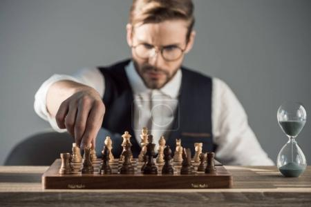 selective focus of focused young businessman playing chess