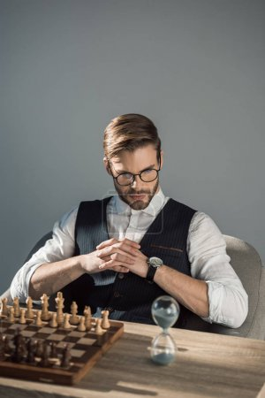 concentrated young businessman looking at sand clock while playing chess