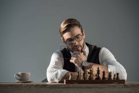 handsome young businessman with hand on chin looking at chess board