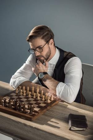 stylish young businessman with hand on chin looking at chess board