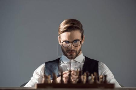 selective focus of young businessman in eyeglasses looking at chess board with pieces