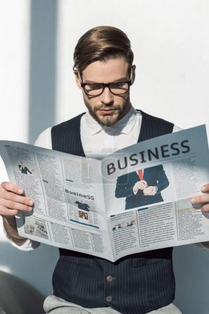 portrait of stylish young businessman in eyeglasses reading newspaper