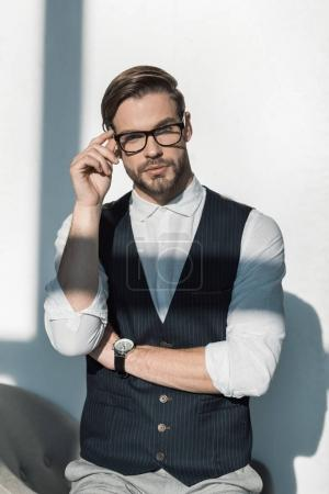 Photo for Portrait of stylish young businessman adjusting eyeglasses and looking at camera - Royalty Free Image
