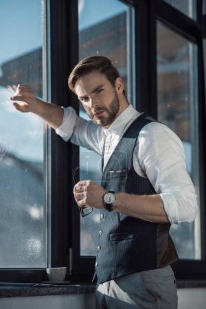 portrait of stylish young businessman holding eyeglasses and looking at camera