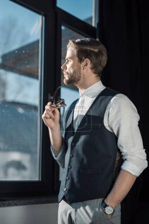 Photo pour Portrait d'homme d'affaires jeune songeur tenant des lunettes et regardant la fenêtre - image libre de droit