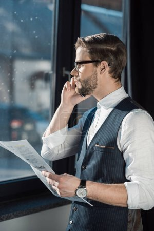 portrait of stylish young businessman holding newspaper and talking by smartphone