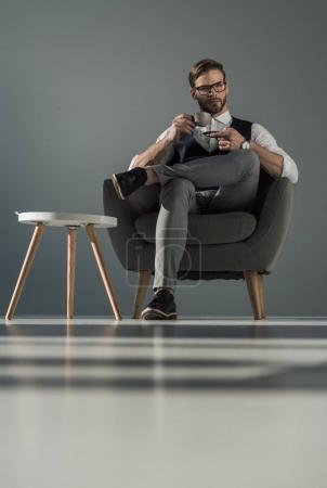 Photo pour Vue à angle bas de l'homme d'affaires élégant avec tasse de café assis dans le fauteuil - image libre de droit