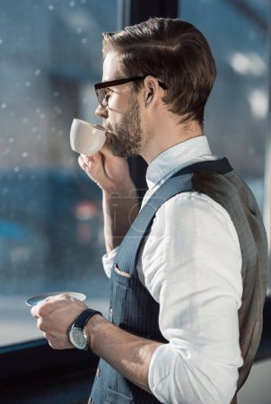 portrait of fashionable young businessman in eyeglasses drinking coffee
