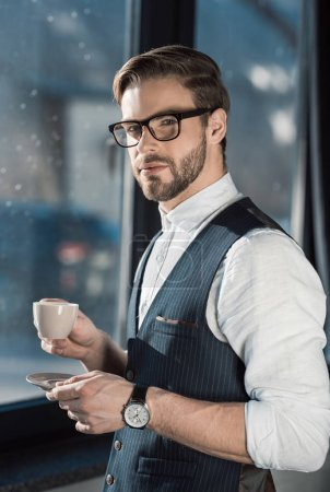 portrait of stylish young businessman in eyeglasses drinking coffee