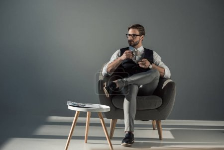 Photo for Handsome stylish young man sitting in armchair and looking away while drinking coffee - Royalty Free Image