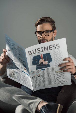 portrait of stylish young businessman in eyeglasses reading newspaper isolated on grey