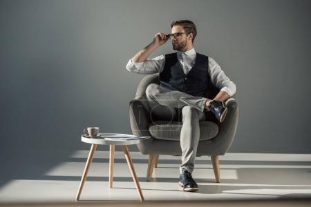 vue pleine longueur de beau jeune homme élégant assis dans un fauteuil et regardant loin