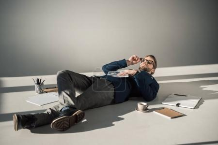 full length view of young businessman in eyeglasses holding newspaper and lying on floor