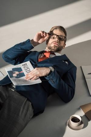 high angle view of handsome stylish young businessman with newspaper lying on floor