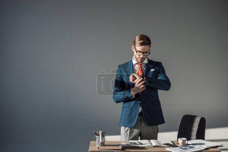 Photo pour Portrait du beau jeune homme d'affaires contrôle montre-bracelet au travail sur fond gris - image libre de droit
