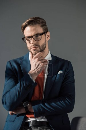 portrait of pensive young businessman in eyeglasses holding hand on chin isolated on grey
