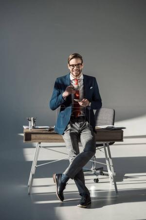homme d'affaires élégant souriant avec tasse de café assis sur la table et regardant la caméra sur gris