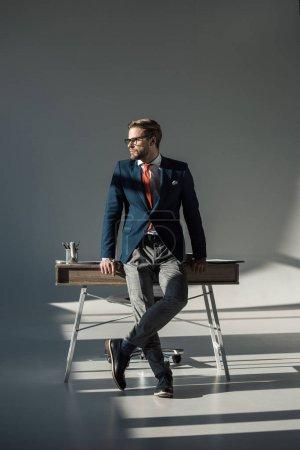 Photo pour Élégant jeune entrepreneur en vêtements assis sur la table et de la recherche. - image libre de droit