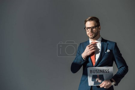 Photo for Handsome young man in eyeglasses holding newspaper and adjusting necktie isolated on grey - Royalty Free Image