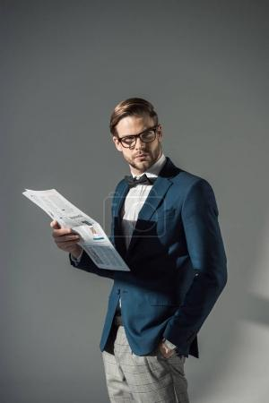 portrait of handsome fashionable businessman in spectacles reading newspaper on grey