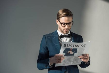 portrait of handsome stylish businessman in spectacles reading newspaper on grey