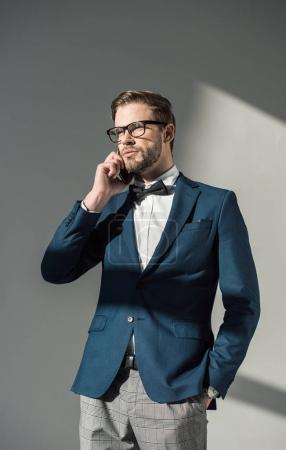 portrait of handsome stylish businessman in spectacles talking by smartphone on grey