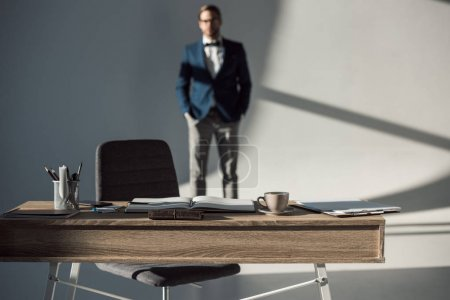 selective focus of table with office supplies and open notebook and businessman standing behind