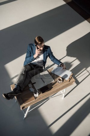 high angle view of businessman talking on smartphone while sitting at workplace