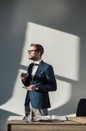 stylish young businessman in eyeglasses drinking coffee at workplace