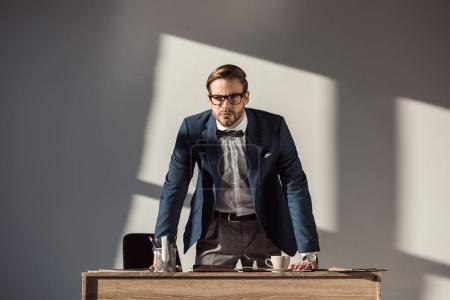 stylish young businessman in eyeglasses leaning at table and looking at camera