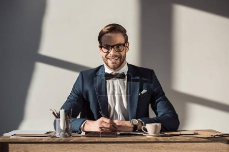 handsome young businessman smiling at camera while sitting at workplace