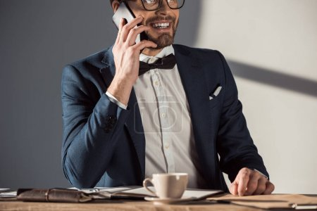 smiling young businessman in eyeglasses and bow tie talking on smartphone