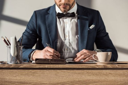 cropped shot of stylish businessman in suit and bow tie writing in notebook