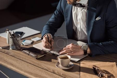 cropped shot of fashionable businessman writing in notebook at workplace