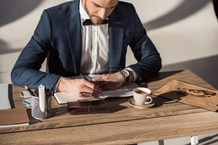 cropped shot of businessman writing in notebook while sitting at table