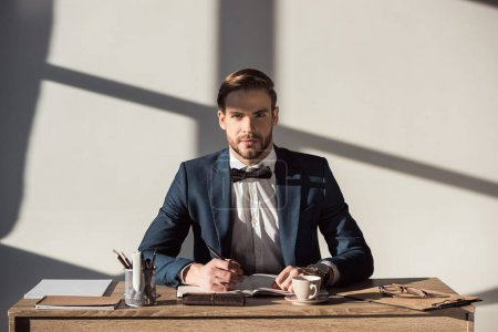 handsome stylish businessman looking at camera while writing in diary at workplace