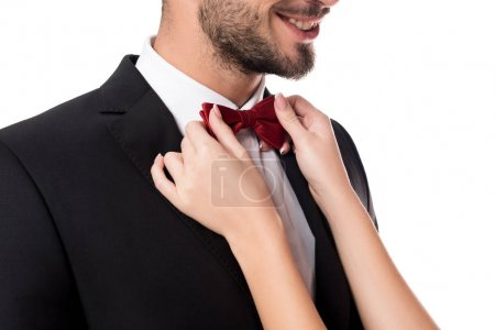 cropped image of girlfriend fixing boyfriends tie bow isolated on white