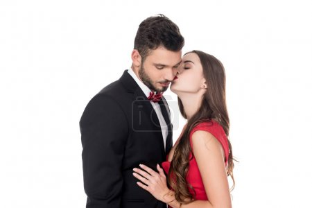 side view of girlfriend kissing boyfriends cheek isolated on white