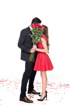 Foto de Pareja heterosexual besándose y que cubre la cara con ramo de flores aisladas en blanco, concepto de día de San Valentín - Imagen libre de derechos